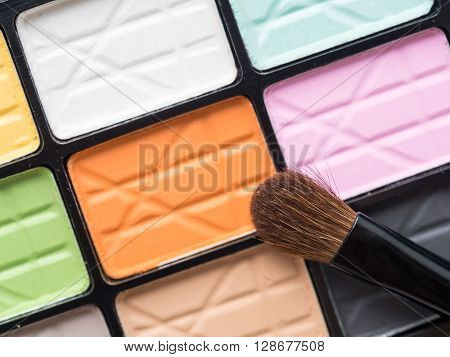 Close up eye make up brush on colorful eye shadow palette - beauty makeup cosmetics