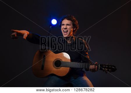 Happy man with guitar pointing finger on somebody over dark background