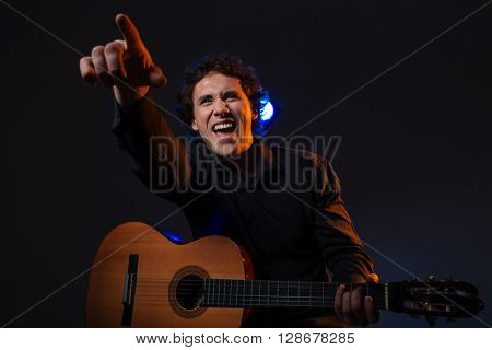 Cheerful man with guitar pointing finger on somebody over dark background