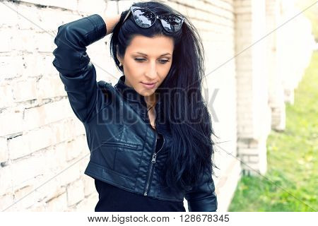 Beautiful brunette girl standing at white brick wall. She dreams, smiling, thinking about beauty. SShe is dressed in black leather jacket. Look down