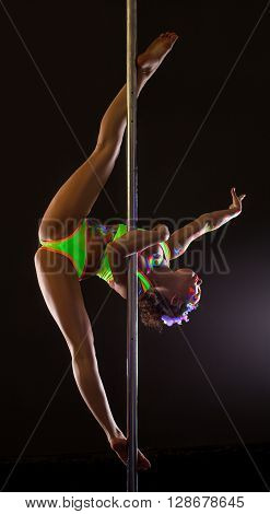 Flexible girl posing while doing gymnastic split on pylon