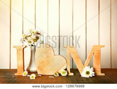 I love mom inscription made of wooden letters with heart on light wooden background