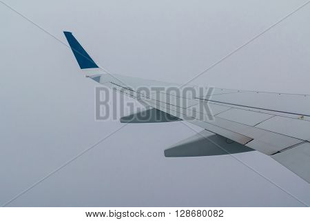 The wing of airplane surrounded by gray fog of clouds