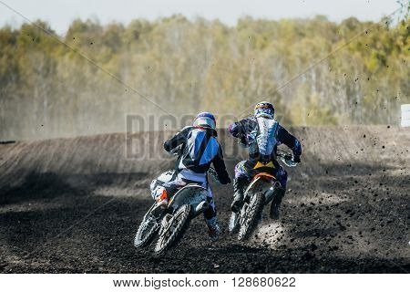 two racer on motorcycles driving on dusty track during competition at races