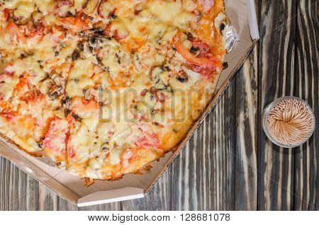 fresh pizza in a box on a background of the old wooden table and toothpicks