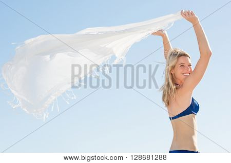 Woman waving white scarf in wind at beach. Young happy woman in bikini standing holding scarf in hand. Young woman playing with the scarf before going for a swim.