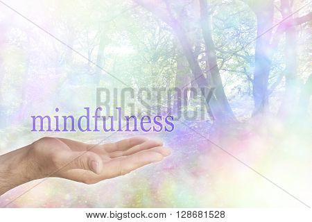 Mindfulness in Nature - male hand palm up with a purple MINDFULNESS word floating above and a rainbow colored bokeh effect woodland scene behind