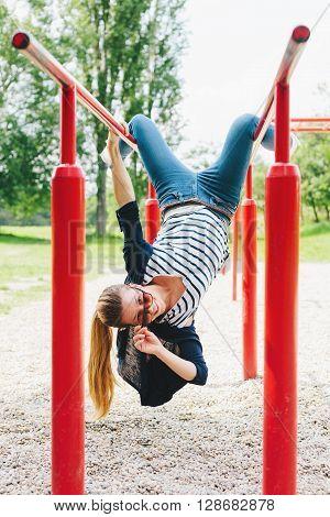 Playful young woman on horizontal bars feeling energetic