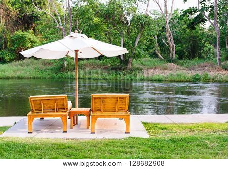 Two daybed with white umbrella along river side