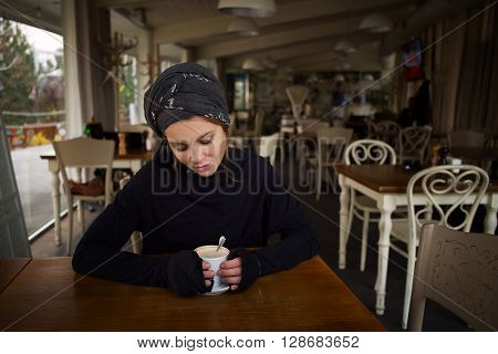 Beautiful Arab girl is drinking coffee in a cafe. She sits at a table in a restaurant and drink coffee in soft sunlight from the window.