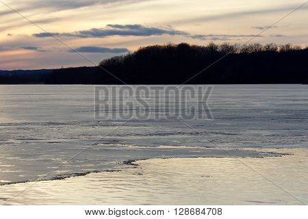 Picture with a beautiful sunset on the icy lake and black trees