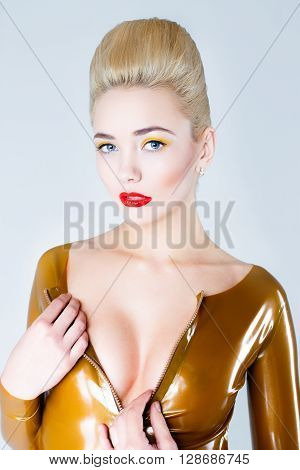 Pretty blonde female model face with artistic make up. Woman with red lips, white hair and pale skin