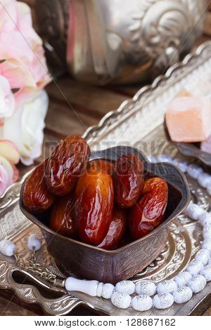 Date fruit with white  rosemary and flowers on oriental traditional tray