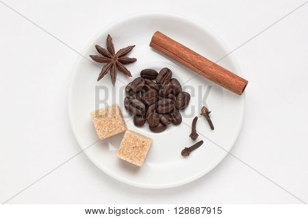 White saucer with coffee beans, cinnamon stick, star anise, cloves and cane sugar against white background, top view with place for text