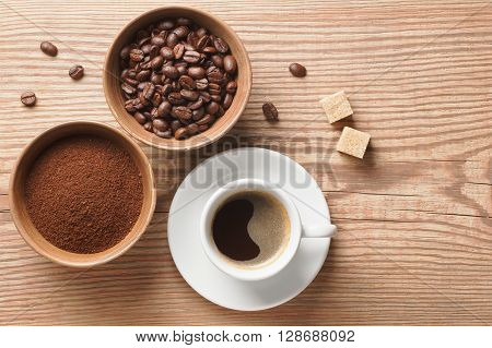 Coffee beans, ground coffee and cup of brewed coffee on rustic wooden table decorated with cane sugar cubes and coffee beans, view from above with space for text