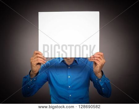 Business man holding a white sign in front of his face