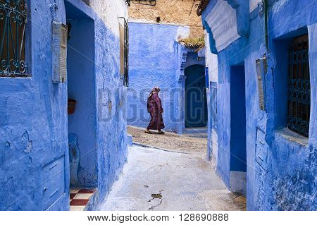 Chefchaouen Morocco - April 10 2016: A woman walking in a street of the town of Chefchaouen in Morocco.