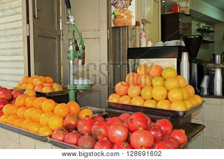 An open air drink stand with oranges and pomegranates in the Christian quarter of Old Jerusalem, Israel.  Also known as the Muristan.