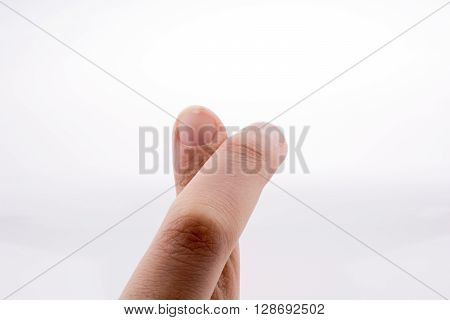 2 crossing fingers on a white background