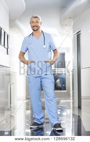 Physiotherapist With Hands In Pockets Standing In Rehab Center
