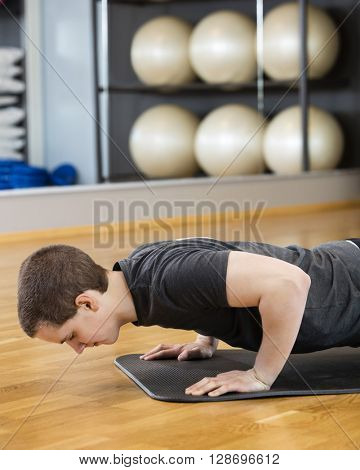 Man Doing Pushups On Mat In Gym
