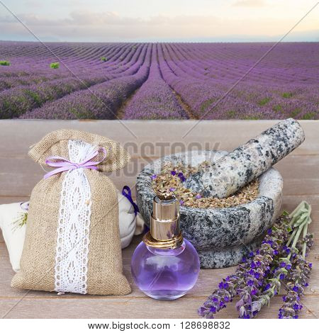 Lavender herbal water in a glass bottle with fresh and dry flowers on  wooden table in lavander garden