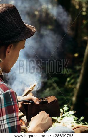 Stylish Hipster Traveler Holding Tobacco And Pipe In Sunny Forest In The Mountains