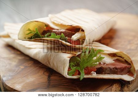 burritos with beef steak, corn, black beans on wood table, vintage toned