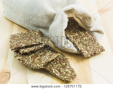 Crisp diet plates made of linen and linen seeds on the wooden board.