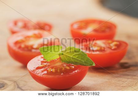 cut in half cherry tomatoes with basil leaf on wood table, vintage toned