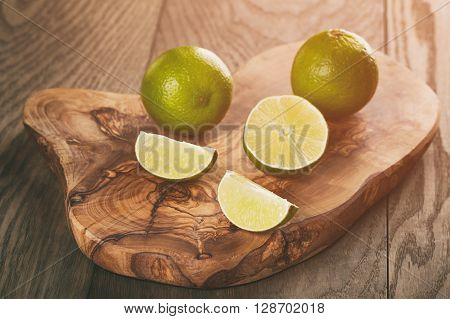 ripe limes on olive board over oak table, vintage toned