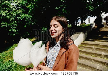 Happy Stylish Girl Holding Big Cotton Candy And Laughing In Amusement Park In Sunny Spring Time