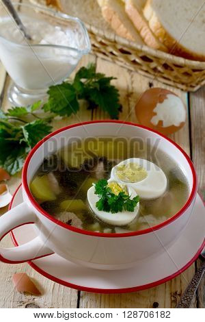 Soup Of Young Nettle With Egg And Sour Cream On A Wooden Background.