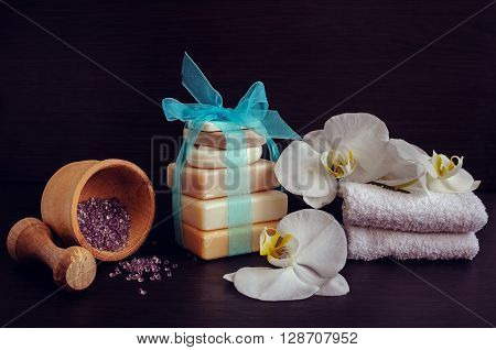 Composition of spa treatment on dark wooden background. Spa and wellness setting in white ans blue colors with natural homemade soaps wooden pounder flowers and soft towels. Selective focus.