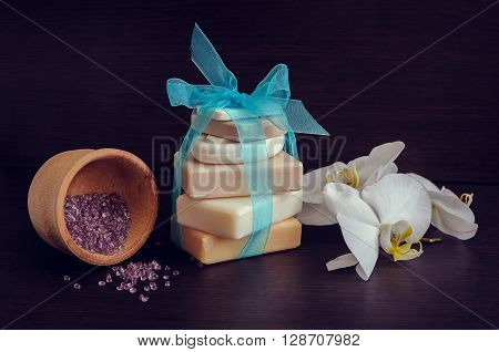 Spa setting in purple and blue colors with different kind of natural soaps orchid and the wooden pounder on dark wooden background. Tower stack of different handmade soaps. Selective focus.