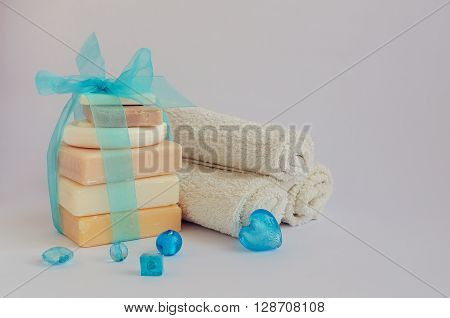 Spa setting with different kind of natural soaps and towels in pastel and blue colors on white background. Tower stack of different handmade soaps. Selective focus. Copy space.