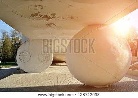 Architecture futuristic complex - stone ball and hemisphere holding up the sloping shaped ceiling under bright sunlight. Modern architecture background.