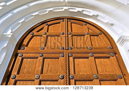 Architecture elements. Aged wooden door with metal rivets and arch of white stone - architecture background