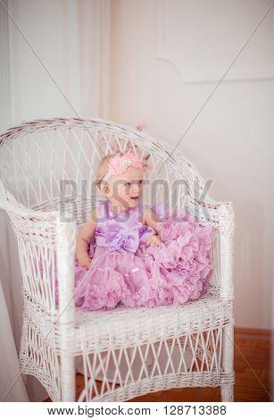 Portrait of little beautiful girl in lilac dress lilac dress