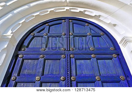 Architecture texture background. Aged wooden dark blue door with metallic rivets and upper arch of white stone - colored architecture background