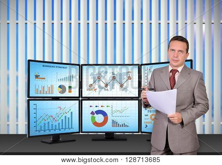 trader standing near trading station which consists of four screens with financial data.
