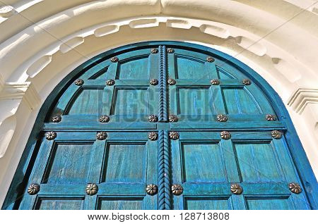 Architecture texture background. Aged wooden turquoise door with steel rivets and uppper arch of white stone - colorful architecture background