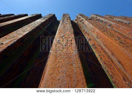 Rusty metal groynes in sea defense wall