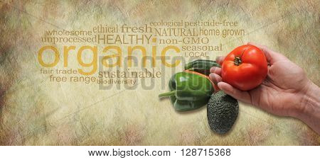Offering Organic Fresh Produce Website Header - male hand holding a beef tomato on a rustic background with an organic word cloud behind and copy space beneath