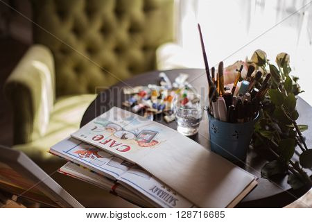workplace of the painter artist a work desk with sketch and tools at home or in studio.