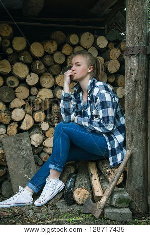 Young woman sitting outdoors on the background of stacked firewood and thinking