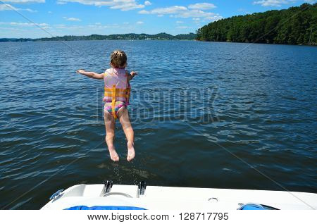 Young girl jumping off the back of a boat into lake water
