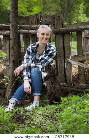 Portrait of a beautiful Young happy smiling teenage girl sitting outdoors near fence with black cat ** Note: Soft Focus at 100%, best at smaller sizes