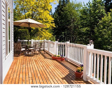 Home outdoor cedar deck with furniture and open umbrella during nice bright day. Horizontal layout.