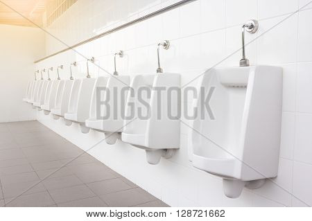 modern restroom interior with urinal row. Toilet background.
